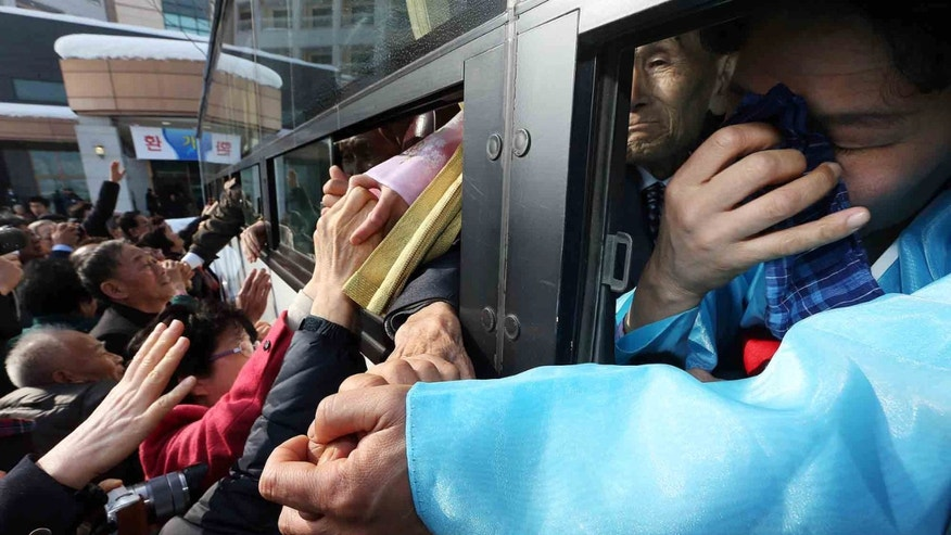 An unidentified North Korean woman on a bus weeps as she holds her South Korean relative's hand after the Separated Family Reunion Meeting at Diamond Mountain in North Korea, Tuesday, Feb. 25, 2014.  The first reunions of North and South Koreans in more than three years have been held in North Korea. The final group of Koreans to participate in reunions ends Tuesday. (AP Photo/Yonhap, Lee Ji-eun)  KOREA OUT