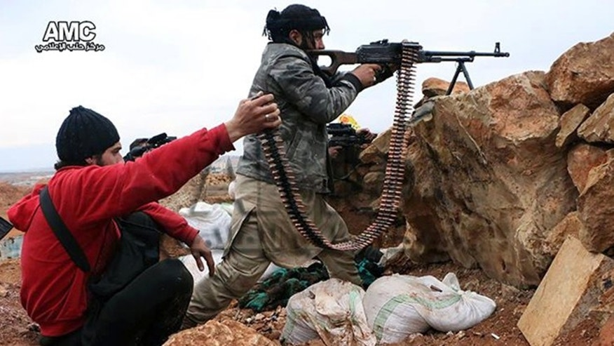 Feb. 25, 2014: This photo provided by the anti-government activist group Aleppo Media Center (AMC), which has been authenticated based on its contents and other AP reporting, shows Syrian rebels firing weapons towards Syrian government troops loyal to President Bashar Assad in Aleppo, Syria.