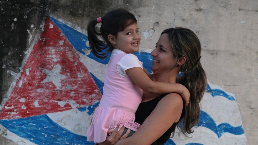 In this Feb. 19, 2014 photo, Yanitse Garcia and her daughter Olivia pose for a photo backdropped by a mural of a Cuban flag in Havana, Cuba. Garcia has spent three decades correcting people on the pronunciation and spelling of her first name. So when her firstborn came into the world three years ago, Garcia decided to save her daughter a lifetime of grief by choosing a simple name that everyone knows and which flows off the tongue: Olivia. (AP Photo/Franklin Reyes)