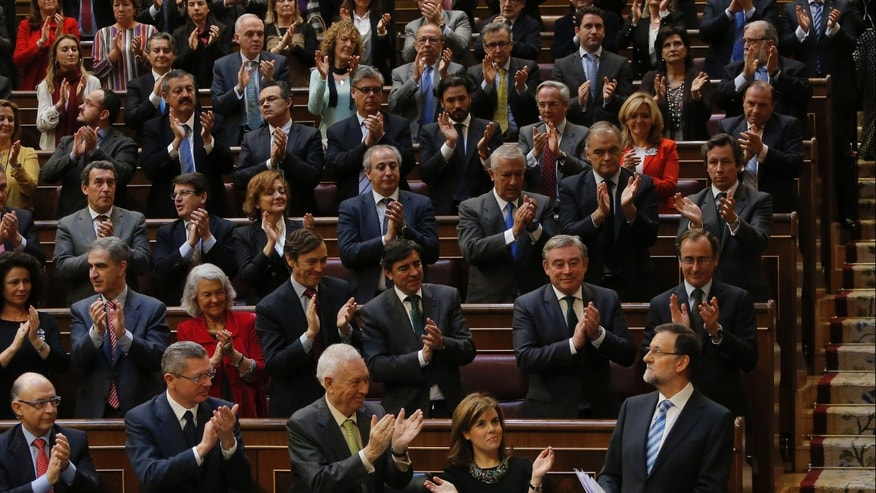 Spain's Prime Minister Mariano Rajoy, bottom right, looks at members of his Party as they celebrates his speech during a state of the nation debate at the Spanish Parliament in Madrid, Spain, Tuesday, Feb. 25, 2014. Prime Minister Mariano Rajoy has revised Spain's economy growth for 2014 upward to 1 percent and announced tax reduction reforms and job creation incentives to give the country a boost after punishing years of recession. Spain's economy began to crumble in 2008 with the collapse of its bloated real-estate sector. It emerged from a two-year recession late last year. (AP Photo/Andres Kudacki)