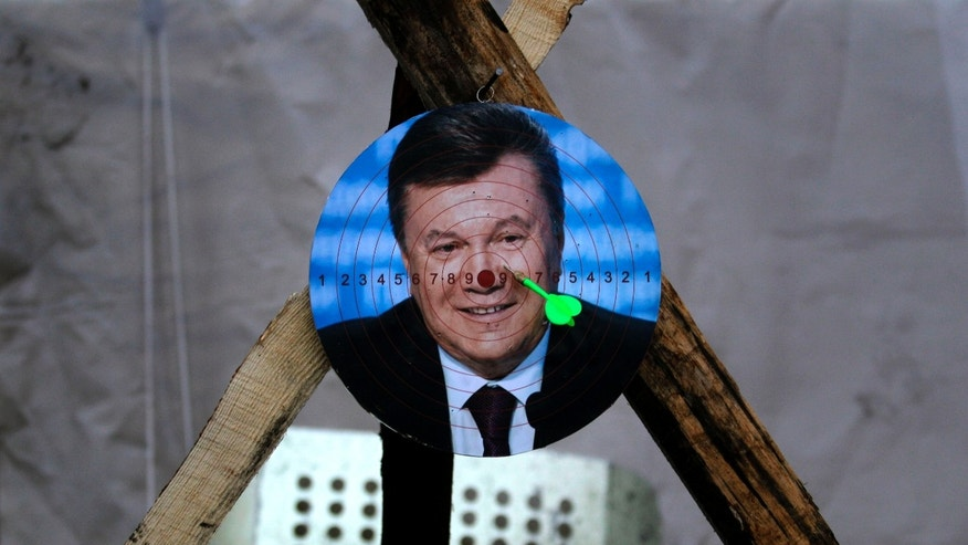 A portrait of Ukraine's embattled president Viktor Yanukovych is used for a game of darts at Independence Square in Kiev, Ukraine, Monday, Feb. 24, 2014. Ukraine's acting government issued an arrest warrant Monday for Yanukovych, accusing him of mass crimes against the protesters who stood up for months against his rule. (AP Photo/ Marko Drobnjakovic)