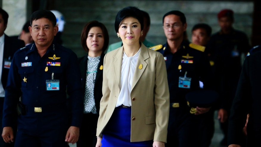 Prime Minister Yingluck Shinawatra, center, leaves the Thai Air Force headquarters after a cabinet meeting in Bangkok, Thailand, Tuesday, Feb. 25, 2014. Anti-government protesters are pressing for the resignation of Yingluck and want her to be replaced by an appointed interim government to implement reforms they say are needed to fight corruption and permanently remove Yingluck's wealthy family from politics. (AP Photo/Wason Wanichakorn)