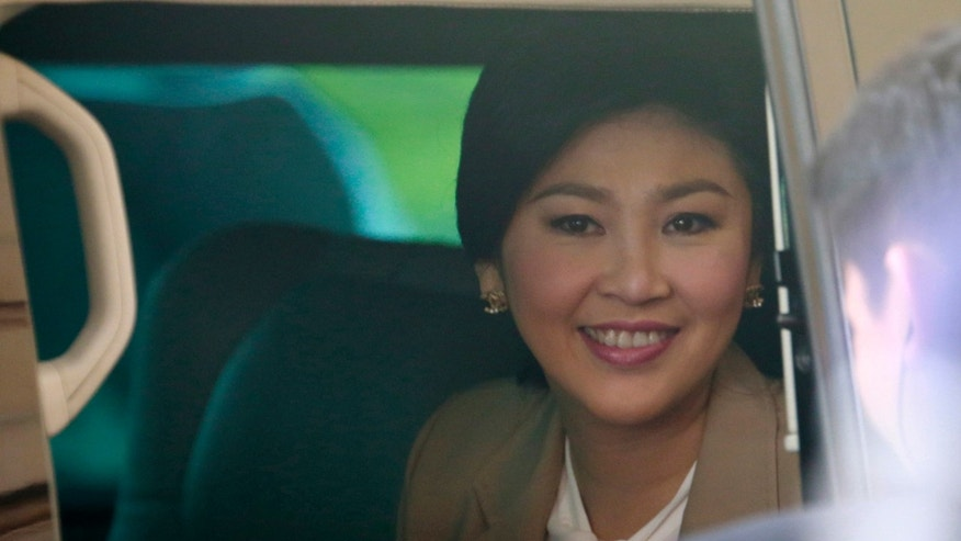 Prime Minister Yingluck Shinawatra sits in a car as she leaves the Thai Air Force headquarters after a cabinet meeting in Bangkok, Thailand, Tuesday, Feb. 25, 2014. Anti-government protesters are pressing for the resignation of Yingluck and want her to be replaced by an appointed interim government to implement reforms they say are needed to fight corruption and permanently remove Yingluck's wealthy family from politics. (AP Photo/Wason Wanichakorn)