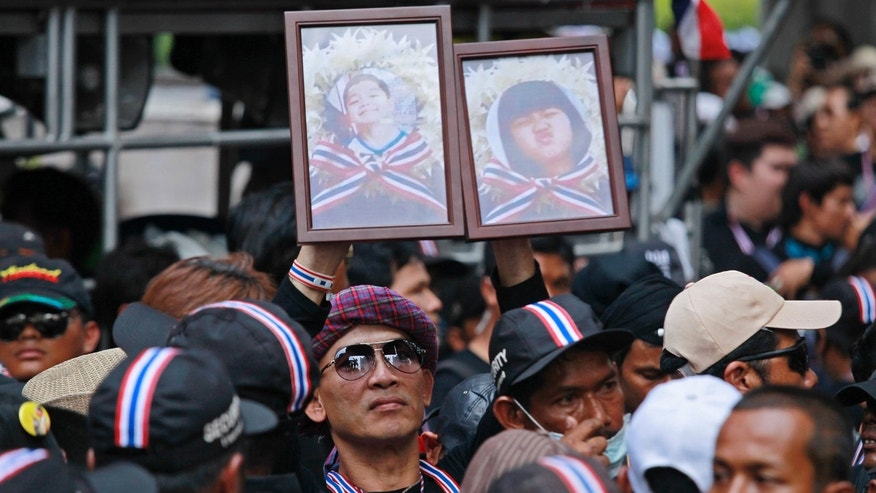 Anti-government supporters hold portraits of children killed in recent blast attacks during a memorial outside the police headquarters in Bangkok, Thailand, Wednesday, Feb. 26, 2014. Violence spread Tuesday to another anti-government protest site in Thailand's capital following weekend explosions that left five people dead, including four children, security officials said. (AP Photo/Wally Santana)
