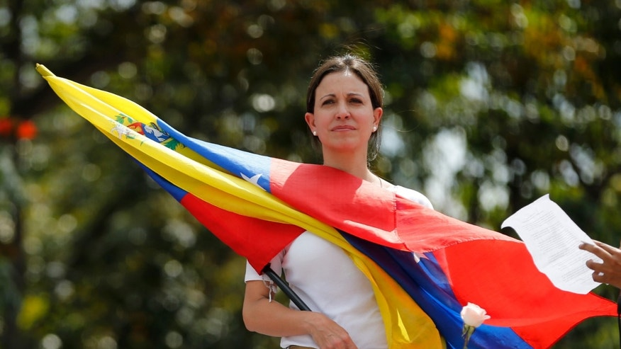 Opposition leader and Congresswoman Maria Corina Machado holds a Venezuelan flag during a women's protest outside the Bolivarian National Guard headquarters in Caracas, Venezuela, Wednesday, Feb. 26, 2014. Former U.S. President Jimmy Carter is expressing concern about Venezuela's escalating political crisis and wants to meet with leaders on both sides in an upcoming trip. (AP Photo/Fernando Llano)