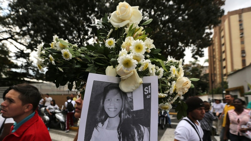 A demonstrator holds a picture of slain student Geraldine Moreno during a women's march to the Bolivarian National Guard headquarters to protest repression against anti-government demonstrators in Caracas, Venezuela, Wednesday, Feb. 26, 2014. Moreno was near her home in Valencia last week, watching students defend a barricade at the corner of her street, when national guardsmen rushed in and fired rubber bullets at close range, hitting her in the face. She died from brain injuries on Saturday. (AP Photo/Fernando Llano)