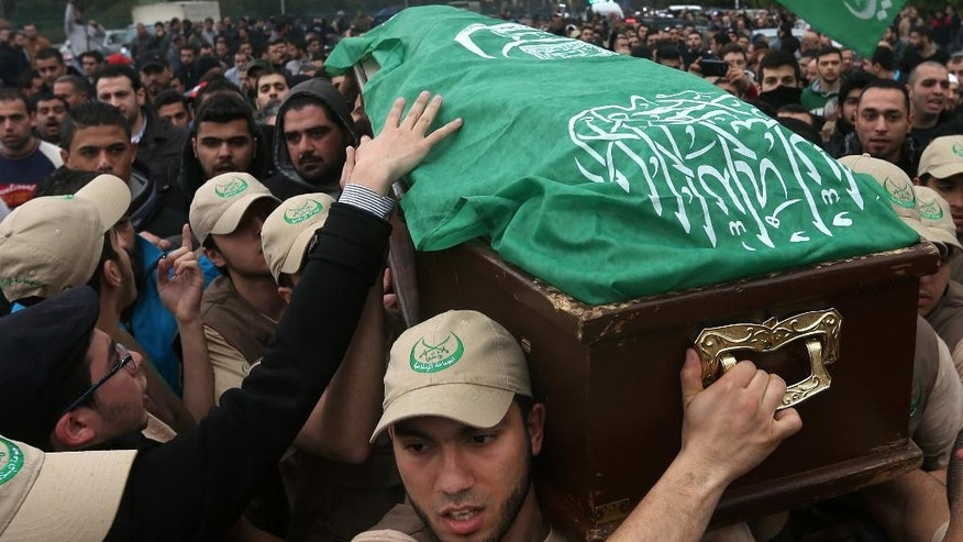 """Members of the Lebanese Sunni society, called the """"Islamic Group,"""" shout slogans as they carry the coffin of Marwan Dimashkieh who was found shot dead on a northern highway on Tuesday after rumors swirled that he was behind a song insulting Hezbollah, during his funeral procession, in Beirut, Lebanon, Wednesday, Feb. 26, 2014. Hundreds of grim mourners gathered in a Beirut cemetery to bury a Sunni Lebanese man rumored to have been the voice of a popular song against rival Shiite group Hezbollah. The tense scenes the Martyrs Cemetery on Wednesday were the latest manifestation of the war in neighboring Syria that is badly inflaming sectarian tensions in Lebanon, even creating harsh musical rivalries. (AP Photo/Hussein Malla)"""