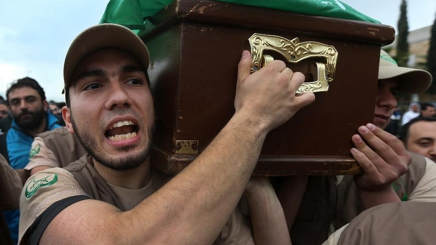 """A Member of the Lebanese Sunni society, called the """"Islamic Group,"""" shouts slogans as he carries the coffin of Marwan Dimashkieh who was found shot dead on a northern highway on Tuesday after rumors swirled that he was behind a song insulting Hezbollah, during his funeral procession, in Beirut, Lebanon, Wednesday, Feb. 26, 2014. Hundreds of grim mourners gathered in a Beirut cemetery to bury a Sunni Lebanese man rumored to have been the voice of a popular song against rival Shiite group Hezbollah. The tense scenes the Martyrs Cemetery on Wednesday were the latest manifestation of the war in neighboring Syria that is badly inflaming sectarian tensions in Lebanon, even creating harsh musical rivalries. (AP Photo/Hussein Malla)"""