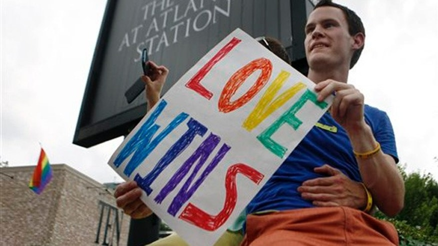 FILE - Int his June 26, 2013 file photo, Daniel Hicks sits on a pillar with his boyfriend to watch the local crowd celebrate the U.S. Supreme Court's rulings on two landmark gay rights cases surrounding same-sex marriage, in Atlanta. Less than two weeks after a federal judge declared Virginiaâs ban on same-sex marriage unconstitutional, a new effort has been launched in the South seeking to build wider acceptance of gay and lesbian couples in the hope of overturning similar bans across the region. (AP Photo/Jaime Henry-White, File)