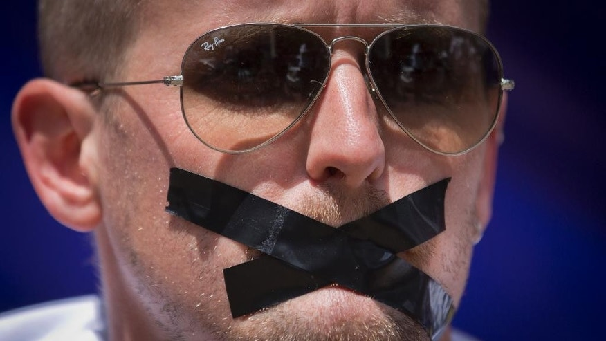 A members of the foreign media wears black tape across his mouth, to signify the silencing of the media, at a demonstration by Kenyan and Nairobi-based foreign media calling for the release in Egypt of detained Al Jazeera journalist Peter Greste and his colleagues, in Nairobi, Kenya Thursday, Feb. 27, 2014. The protest, part of a global day of action in support of press freedom, called for all journalists jailed in Egypt to be freed but focused attention in particular on Greste, a Nairobi-based correspondent for Al Jazeera who has been in custody in Egypt since Dec. 29, 2013. (AP Photo/Ben Curtis)