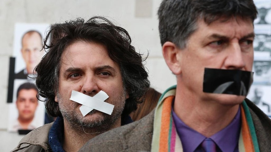 Protesters, wearing tape across their mouths, to signify the silencing of the media, participate in a rally in support of press freedom, and demanding the release of detained journalists in Egypt, in central London, Thursday, Feb. 27, 2014. The protest, part of a global day of action in support of press freedom, called for all journalists jailed in Egypt to be freed. (AP Photo/Lefteris Pitarakis)