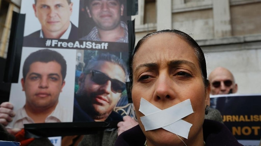 A protester wearing tape across her mouth, to signify the silencing of the media, participates in a rally in support of press freedom, and demanding the release of detained journalists in Egypt, in central London, Thursday, Feb. 27, 2014. The protest, part of a global day of action in support of press freedom, called for all journalists jailed in Egypt to be freed. (AP Photo/Lefteris Pitarakis)