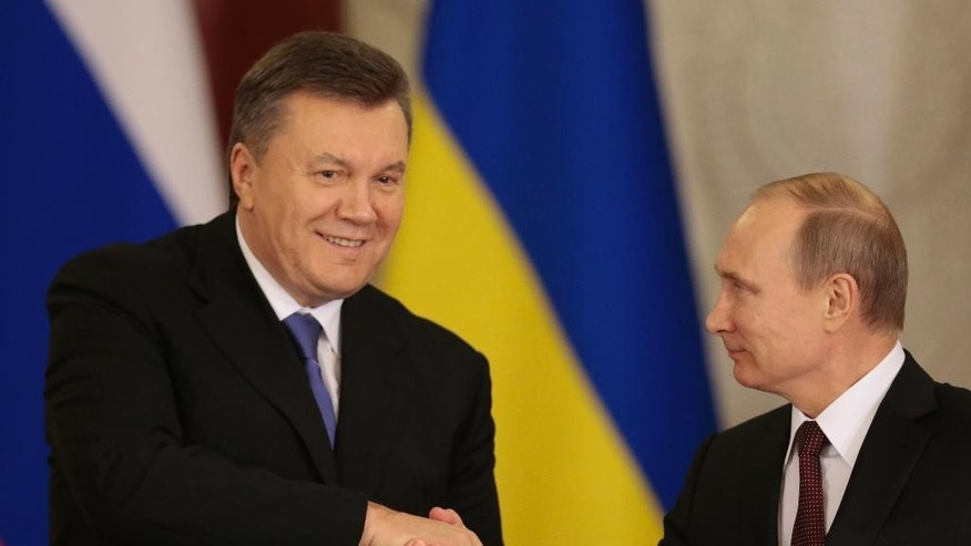 """FILE - In this Tuesday, Dec. 17, 2013 file photo, Russian President Vladimir Putin, right, and his Ukrainian counterpart Viktor Yanukovych shake hands after signing an agreement during their talks in Moscow. Moscow on Wednesday granted Ukrainian President Viktor Yanukovych protection """"on the territory of Russia,"""" shortly after the fugitive leader sought help from the Kremlin, according to an official quoted by Russian news agencies. (AP Photo/Ivan Sekretarev, File)"""