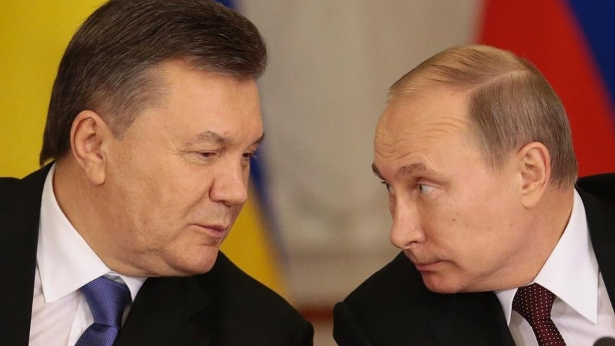 "FILE - In this Tuesday Dec. 17, 2013 file photo, Russian President Vladimir Putin, right, and his Ukrainian counterpart Viktor Yanukovych talk during a news conference in Moscow. Moscow on Wednesday granted Ukrainian President Viktor Yanukovych protection ""on the territory of Russia,"" shortly after the fugitive leader sought help from the Kremlin, according to an official quoted by Russian news agencies. (AP Photo/Ivan Sekretarev, file)"