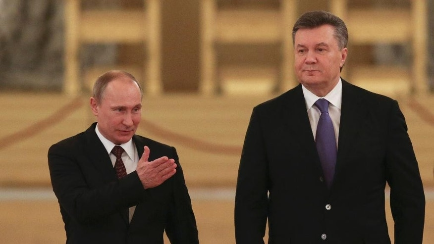 "FILE - In this Tuesday, Dec. 17, 2013 file photo Russian President Vladimir Putin, left, shows the way to his Ukrainian counterpart Viktor Yanukovych during a meeting in the Kremlin in Moscow, Russia. Moscow on Wednesday granted Ukrainian President Viktor Yanukovych protection ""on the territory of Russia,"" shortly after the fugitive leader sought help from the Kremlin, according to an official quoted by Russian news agencies. (AP Photo/Sergei Karpukhin, Pool, file)"