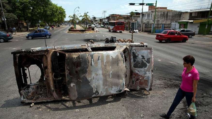 A woman glances over at a charred car turned on its side, that was set on fire by anti-government protesters overnight, in Valencia, Venezuela, Thursday, Feb. 27, 2014. In the past two weeks, clashes between protesters and security forces loyal to the president have left 16 dead, and opposition leader Leopoldo Lopez has been thrown in jail. (AP Photo/Rodrigo Abd)