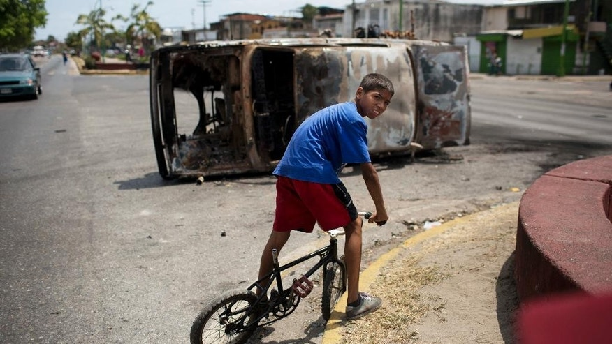A boy straddles his bike in front of a charred car turned on its side, that was set on fire overnight by anti-government protesters, in Valencia, Venezuela, Thursday, Feb. 27, 2014. In the past two weeks, clashes between protesters and security forces loyal to the president have left 16 dead, and opposition leader Leopoldo Lopez has been thrown in jail. (AP Photo/Rodrigo Abd) (