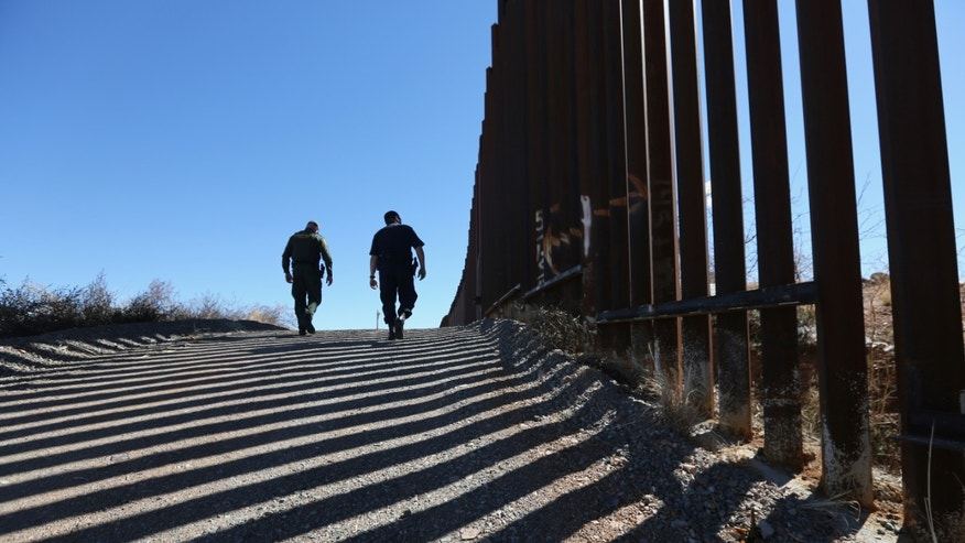 NOGALES, AZ - FEBRUARY 26:  U.S. Customs and Border Protection personnel walk along a section of the recently-constructed fence at the U.S.-Mexico border on February 26, 2013 in Nogales, Arizona. The newest generation of  fencing allows Border Patrol agents to see through the fence and is harder to scale from the Mexican side. (Photo by John Moore/Getty Images)