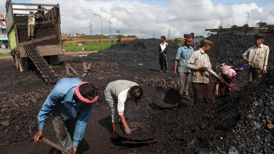 In this July 1, 2013 photo, Indian laborers dig a roadside coal depot at Khliehriet in Meghalaya, India. For six years in a row, India's monopoly coal producer has missed its production targets, leading to chronic electricity shortages and sending power producers scrambling for pricier imports. But what looks like a looming crisis could turn out to be an almost accidental energy overhaul. India has relied for decades on cheap coal to provide electricity for burgeoning industry and fast-expanding cities, putting aside worries about pollution and global warming. (AP Photo/Anupam Nath)
