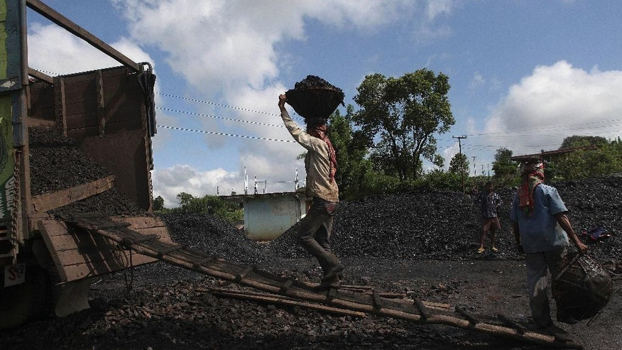 In this July 1, 2013 photo, Indian laborers load coal into a truck at a roadside coal depot at Khliehriet in Meghalaya, India. For six years in a row, India's monopoly coal producer has missed its production targets, leading to chronic electricity shortages and sending power producers scrambling for pricier imports. But what looks like a looming crisis could turn out to be an almost accidental energy overhaul. India has relied for decades on cheap coal to provide electricity for burgeoning industry and fast-expanding cities, putting aside worries about pollution and global warming. (AP Photo/Anupam Nath)