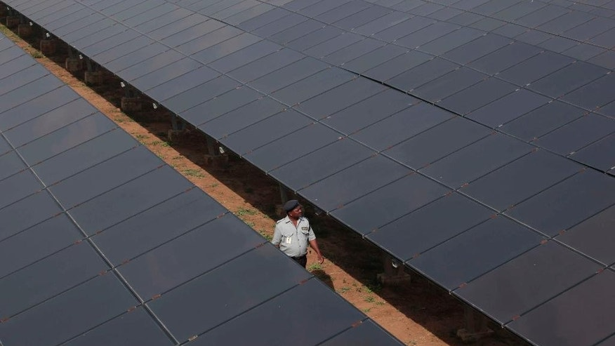 In this Thursday, Feb. 27, 2014 photo, an Indian security man walks amid solar panels at a solar power project site in Raisan village near Gandhinagar, India. India has relied for decades on cheap coal to provide electricity for burgeoning industry and fast-expanding cities, putting aside worries about pollution and global warming. But from three years ago when solar capacity was almost zero, the country has added 2.2 gigawatts of solar to its electricity grid, enough to power 20 million Indian homes. (AP Photo/Ajit Solanki)