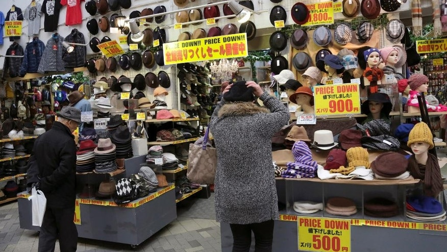 In this Monday, Feb. 17, 2014 photo, a woman tries out a hut for sale a discount store in Tokyo. Japan's consumer price index rose 1.3 percent in January and factory production also climbed, suggesting the recovery in the world's third-largest economy is holding steady ahead of an April 1 tax hike. A raft of data released Friday suggest the economy may need still more help in weathering the 3 percent tax increase in April as many economists forecast a contraction will follow as consumers and businesses adjust to higher costs. (AP Photo/Shizuo Kambayashi)