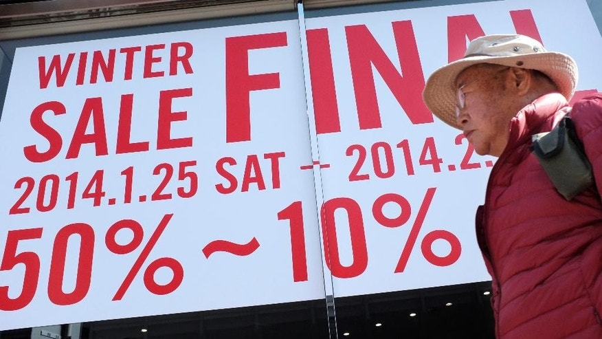 In this Monday, Feb. 17, 2014 photo, a man walks by a clothing store with a winter sale advertisement in Tokyo. Japan's consumer price index rose 1.3 percent in January and factory production also climbed, suggesting the recovery in the world's third-largest economy is holding steady ahead of an April 1 tax hike. A raft of data released Friday suggest the economy may need still more help in weathering the 3 percent tax increase in April as many economists forecast a contraction will follow as consumers and businesses adjust to higher costs. (AP Photo/Shizuo Kambayashi)