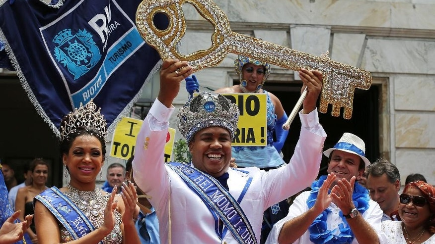 Flanked by Carnival Queen Leticia Martins Guimaraes and Rio de Janeiro's Mayor Eduardo Paes, a crowned and costumed Wilson Dias da Costa Neto, the 2014 King Momo or Carnival King, holds up the key to the city at a ceremony marking the official start of Carnival, in Rio de Janeiro, Brazil, Friday, Feb. 28, 2014. (AP Photo/Leo Correa)