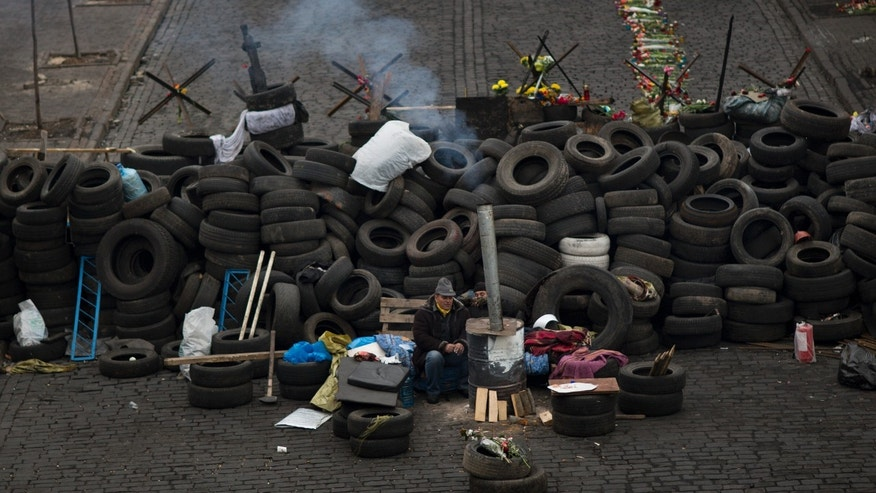 Feb. 28, 2014 - An anti-Yanukovych protester warms himself next to a fire as he guards a barricade in a street heading to Kiev's Independence Square, the epicenter of the country's current unrest.