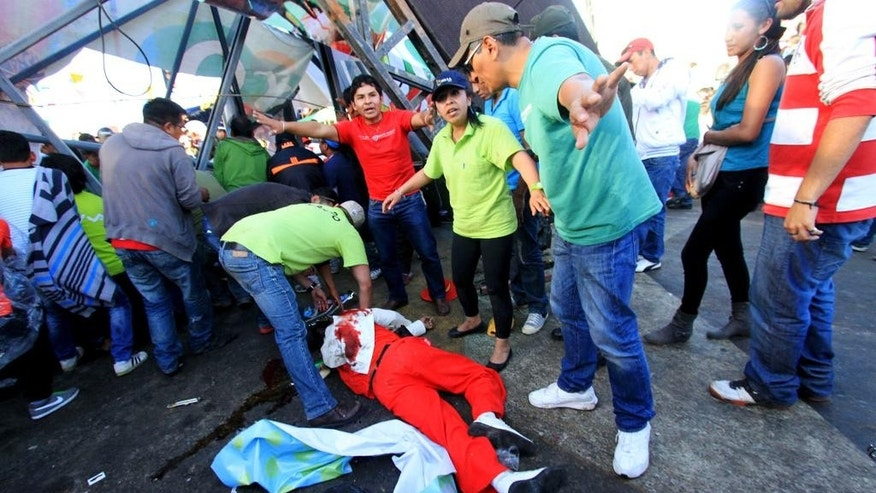 People come to the aid of a musician injured during a carnival celebrations in Oruro, Bolivia, Saturday, March 1, 2014. Bolivian authorities say four people were killed and more than 60 injured when an overloaded metal footbridge collapsed onto a group of musicians marching in the opening parade of Carnival in the highlands city of Oruro. (AP Photo/Alejandra Rocabado)