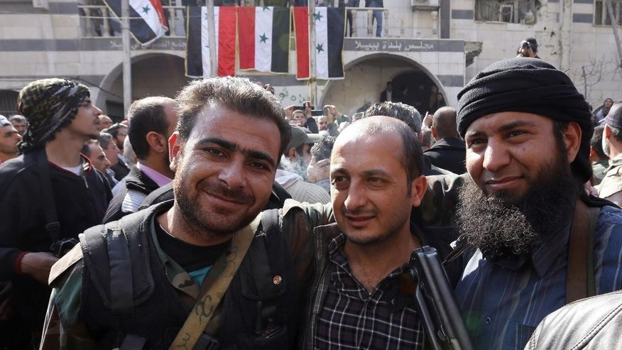 "In this Monday Feb. 17, 2014 photo, Syrian rebels, right, stands with two soldiers from Syrian government forces, center and left, as they pose for a picture after a reconciliation agreement between the two groups, in Babila, southeast Damascus, Syria. In one besieged neighborhood after another, weary rebels have turned over their weapons to the Syrian government in exchange for an easing of suffocating blockades that have prevented food, medicine and other staples from reaching civilians trapped inside. The government touts the truces as part of its program of ""national reconciliation"" to end Syria's crisis, which has killed more than 140,000 people since March 2011. (AP Photo)"