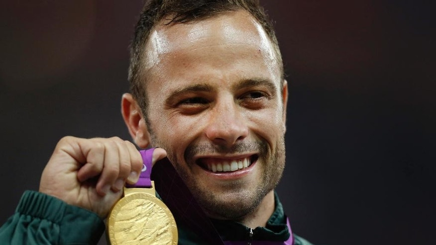 FILE - In this Saturday, Sept. 8, 2012, file photo, Gold medalist South Africa's Oscar Pistorius poses with his medal during the ceremony after winning the men's 400 meters T44 category final during the athletics competition at the 2012 Paralympics, in London. With his athletic triumphs tarnished by the killing of his girlfriend, Reeva Steenkamp. Pistorius, now 27, faces possibly being sent to prison until he is older than 50. Pistorius goes on trial Monday March 3, 2014.   (AP Photo/Matt Dunham, File)