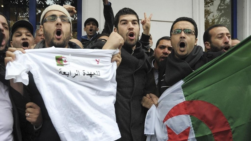 "Protesters display a T-shirt  reading ""No to a 4th mandate"" and an Algerian flag during a demonstration against President Bouteflika's fourth candidacy in the presidential election,  in Algiers, Saturday, March 1, 2014. Algerian President Abdelaziz Bouteflika, 76, has not appeared in public for two years and is visibly weaker since suffering a stroke last year. Even so, he is expected to win the April 17 presidential election with the backing of the powerful state apparatus. (AP Photo/ Sidali Djarboub)"
