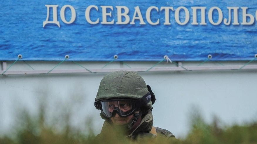 "A gunman in unmarked uniform stands guard as troops take control the the Coast Guard offices in Balaklava, outskirts of Sevastopol, Ukraine, Saturday, March 1, 2014. The word in the background reads ""To Sevastopol"". An emblem on one of the vehicles and their number plates identify them as belonging to the Russian military. Ukrainian officials have accused Russia of sending new troops into Crimea, a strategic Russia-speaking region that hosts a major Russian navy base. (AP Photo/Andrew Lubimov)"