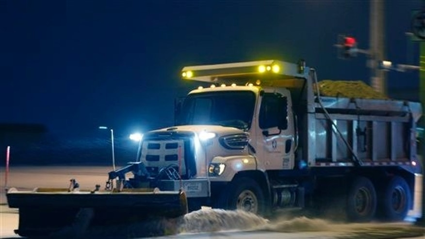A city plow removes snow from an intersection along 6th Street in Lawrence, Kan., Sunday, March 2, 2014. (AP Photo/Orlin Wagner)