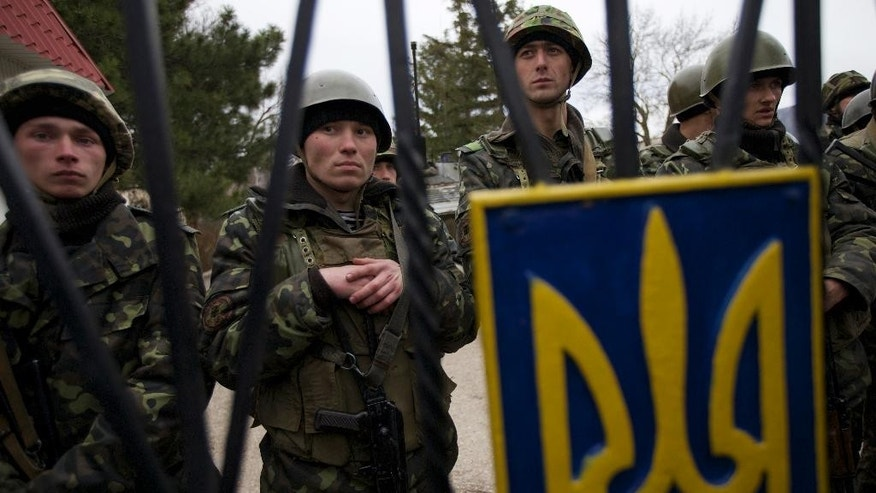 Ukrainian soldiers guard a gate to their military base in the village of Perevalne, outside Simferopol, Ukraine, Sunday, March 2, 2014. Hundreds of armed men in trucks and armored vehicles surrounded a Ukrainian military base Sunday in Crimea, blocking its soldiers from leaving. (AP Photo/Ivan Sekretarev)