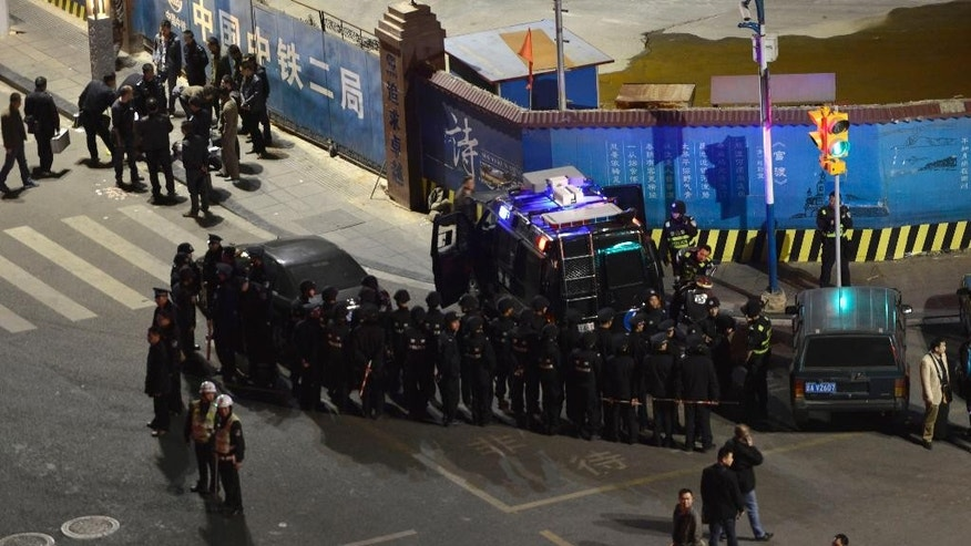 In this photo taken Saturday March 1, 2014, Chinese police officers form up outside a railway station in Kunming in southwestern China's Yunnan province. More than 10 knife-wielding attackers slashed people at the train station in what authorities called a terrorist attack by ethnic separatists in western China, and police fatally shot four of the assailants. (AP Photo)  CHINA OUT
