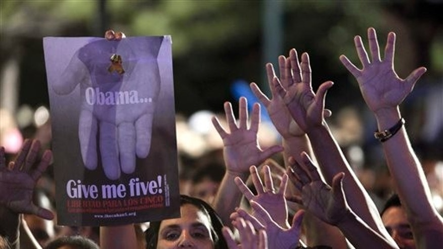 "A woman holds a poster that reads ""Obama give me five"" during a concert in honor of the five intelligence agents in Havana, Cuba, Saturday, March 1, 2014. Thousands of Cubans rallied at the University of Havana on Saturday night for a concert to give a hero's welcome to the second of five intelligence agents to return to the island after completing long prison terms in the United States. (AP Photo/Franklin Reyes)"
