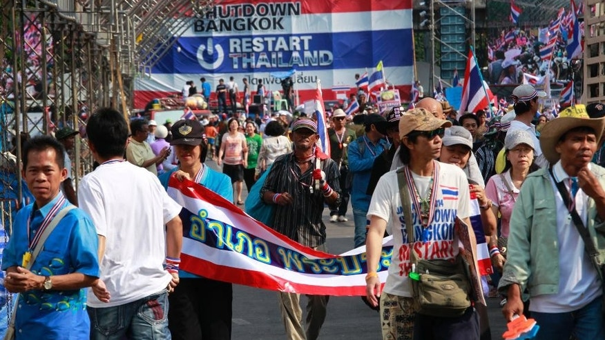 Protesters carrying their belongings participate in the last march from the main protest stage before it is removed from a popular intersection in Bangkok, Thailand, Sunday, March 2, 2014. The anti-government protesters withdrew from several stages erected at key intersections around Bangkok. Starting Monday, they will consolidate at Lumpini Park, a central venue that has become a traditional protest site. (AP Photo/Wally Santana)