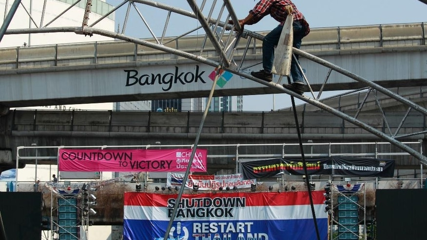 A construction worker disassembles tent frames at the main protest stage before it is removed from a popular intersection in Bangkok, Thailand, Sunday, March 2, 2014. The anti-government protesters withdrew from several stages erected at key intersections around Bangkok. Starting Monday, they will consolidate at Lumpini Park, a central venue that has become a traditional protest site. (AP Photo/Wally Santana)