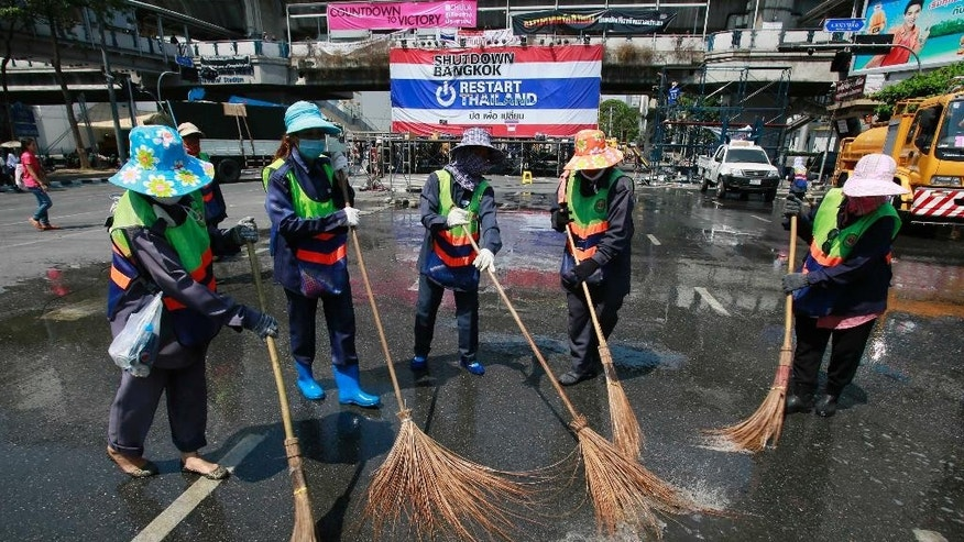 City workers clean a main protest site as it is cleared from a popular intersection in Bangkok, Thailand, Sunday, March 2, 2014. The anti-government protesters withdrew from several stages erected at key intersections around Bangkok. Starting Monday, they will consolidate at Lumpini Park, a central venue that has become a traditional protest site. (AP Photo/Wally Santana)