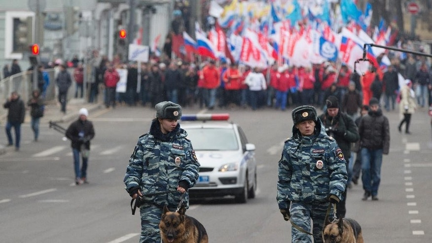 Police officers with dogs walk in front of more than ten thousand pro-Kremlin demonstrators many holding Russian flags march in central Moscow, Russia, Sunday, March 2, 2014 to express support for the latest developments in Russian-Ukrainian relations. (AP Photo/Pavel Golovkin)