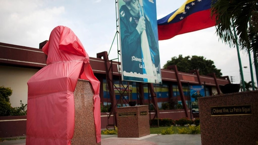 A new bust of former Venezuela's President Hugo Chavez is protected by a red fabric at a Bolivarian National Guard base in Valencia, Venezuela, Saturday, March 1, 2014. To mark Chavez's passing, President Nicolas Maduro has decreed a 10 day-long commemoration - longer than the week-long period of official mourning that followed his death at the age of 58 on March 5, 2013. (AP Photo/Rodrigo Abd)