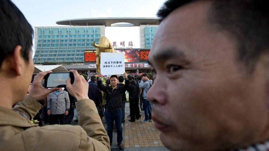 "A man holds a billboard with slogans urging fights against terrorists on a square outside the Kunming Railway Station, where more than 10 assailants slashed scores of people with knives Saturday evening, in Kunming, in western China's Yunnan province, Monday, March 3, 2014. Twenty-nine slash victims and four attackers were killed and 143 people wounded in the attack which officials said was a terrorist assault by ethnic separatists from the far west. Chinese words on the billboard are, ""The spring city under the shine, everybody beats the terrorists."" (AP Photo/Alexander F. Yuan)"