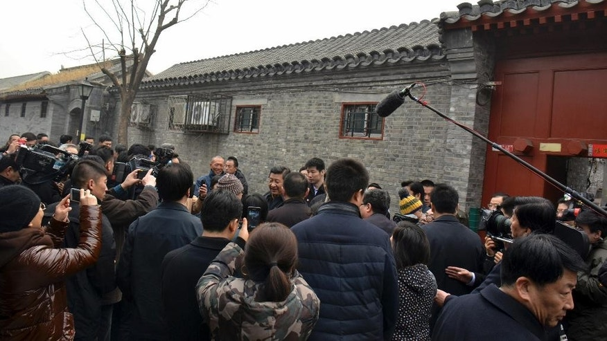 FILE - In this Tuesday Feb. 25, 2014 file photo, Chinese President Xi Jinping, center, is surrounded by onlookers and television crew during an unannounced visit to a residential alley in Beijing. Xi looks more powerful than any Chinese leader in recent decades as his government prepares to deliver its first one-year report card Wednesday, March 5 but a deadly weekend slashing spree by alleged separatists was a reminder of the serious challenges facing his administration. In recent weeks, Xi has put himself in charge of a new top-level party committee focused on steering state security, a panel on driving sweeping economic reforms, and another on cybersecurity. (AP Photo/File) CHINA OUT