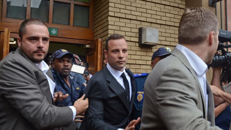 March 3, 2014: Oscar Pistorius, center, is escorted out of the high court after the first day of his trial in Pretoria, South Africa.