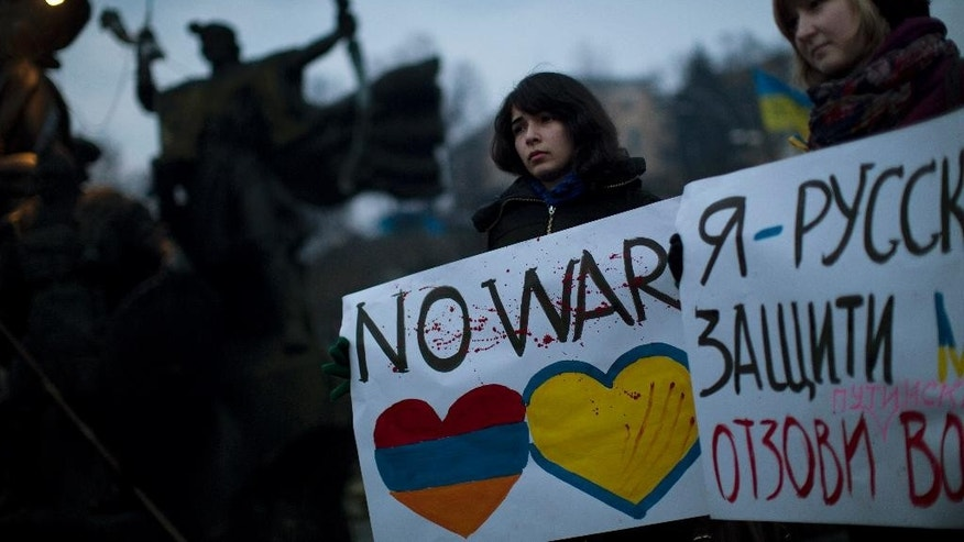 "Ukrainian Maria, 23, right, and Vanui, 22, hold posters against Russia's military intervention in Crimea, in Kiev, Ukraine, Sunday, March 2, 2014. Russia's parliament approved a motion to use the country's military in Ukraine after a request from President Vladimir Putin as protests in Russian-speaking cities turned violent Saturday, sparking fears of a wide-scale invasion. The poster in the right side reads in Ukrainian: ""I am from Russia, please protect me and remove the weapons and soldiers from Ukraine."" (AP Photo/Emilio Morenatti)"