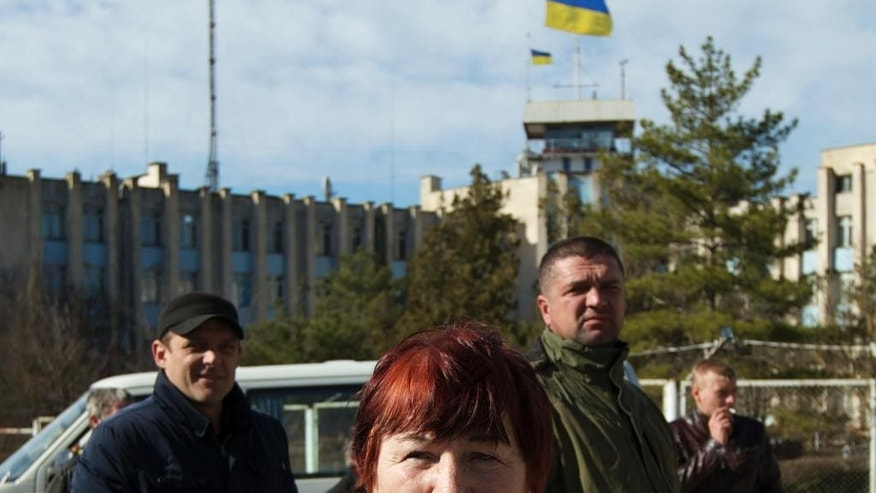 Local residents gather outside the Ukrainian naval base headquarters in the town of Novo-Ozerne, some 90 km west of the Crimean capital Simferopol, Ukraine, on Monday March 3, 2014. For years, the little Crimean town was closed off from the rest of the world, a secretive community, at the edge of a key Soviet naval base, sealed by roadblocks and armed guards. There's not much in town anymore. But the Russians want it. And the little forgotten town is now sharply divided, torn between those who welcomed the arrival here over the weekend of dozens of Russian soldiers wearing unmarked uniforms, and those who back the Ukrainians who are refusing to surrender their weapons. (AP Photo/Ivan Sekretarev)