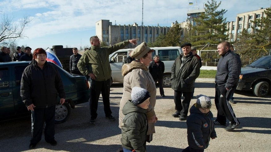 Local residents, some of them pro-Russian supporters, gather outside the Ukrainian naval base headquarters in the town of Novo-Ozerne, some 90 km west of the Crimean capital Simferopol, Ukraine, on Monday March 3, 2014. For years, the little Crimean town was closed off from the rest of the world, a secretive community, at the edge of a key Soviet naval base, sealed by roadblocks and armed guards. There's not much in town anymore. But the Russians want it. And the little forgotten town is now sharply divided, torn between those who welcomed the arrival here over the weekend of dozens of Russian soldiers wearing unmarked uniforms, and those who back the Ukrainians who are refusing to surrender their weapons. (AP Photo/Ivan Sekretarev)