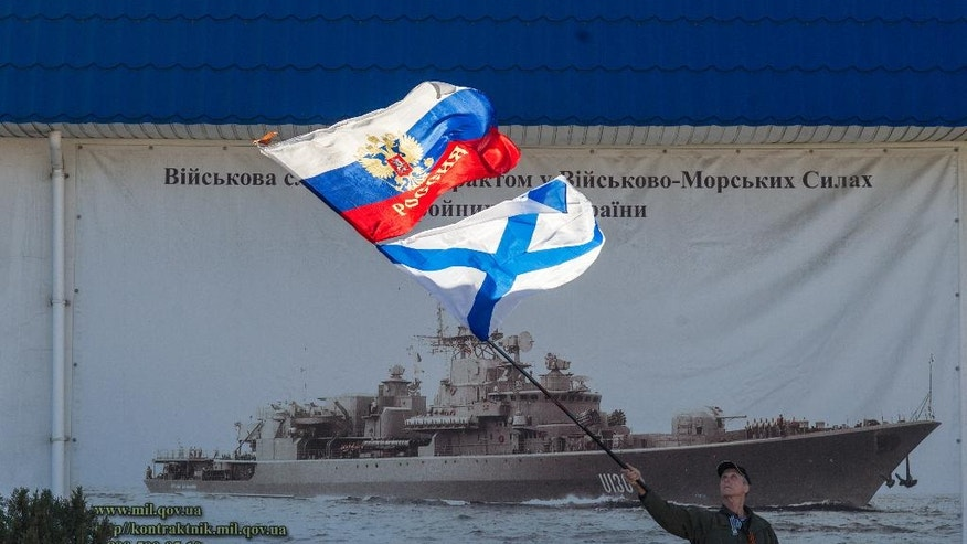 A pro-Russian activist waves the Russian state, upper, and Russian Navy flags outside an entrance to the General Staff Headquarters of the Ukrainian Navy in Sevastopol, Ukraine, Monday, March 3, 2014. Pro-Russian soldiers seem to further cement their control over the strategic region — that also houses the Russian Black Sea Fleet — by seizing a ferry terminal in the Ukrainian city of Kerch about 20 kilometers (12 miles) by boat to Russia, intensifying fears that Moscow will send even more troops into the peninsula. It comes as the U.S. and European governments are trying to figure out ways to halt and reverse the Russian incursion. (AP Photo/Andrew Lubimov)